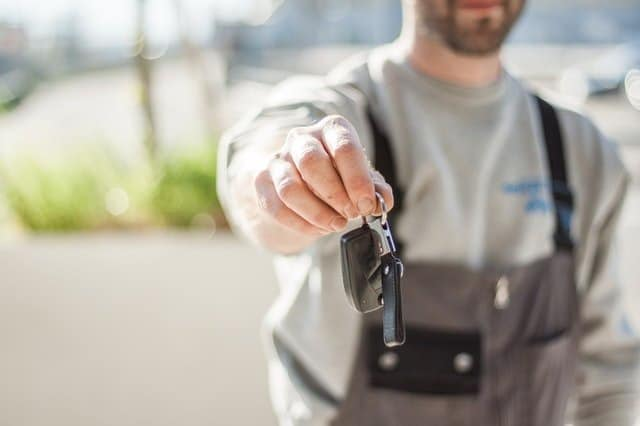 guy handing over car keys to rental car